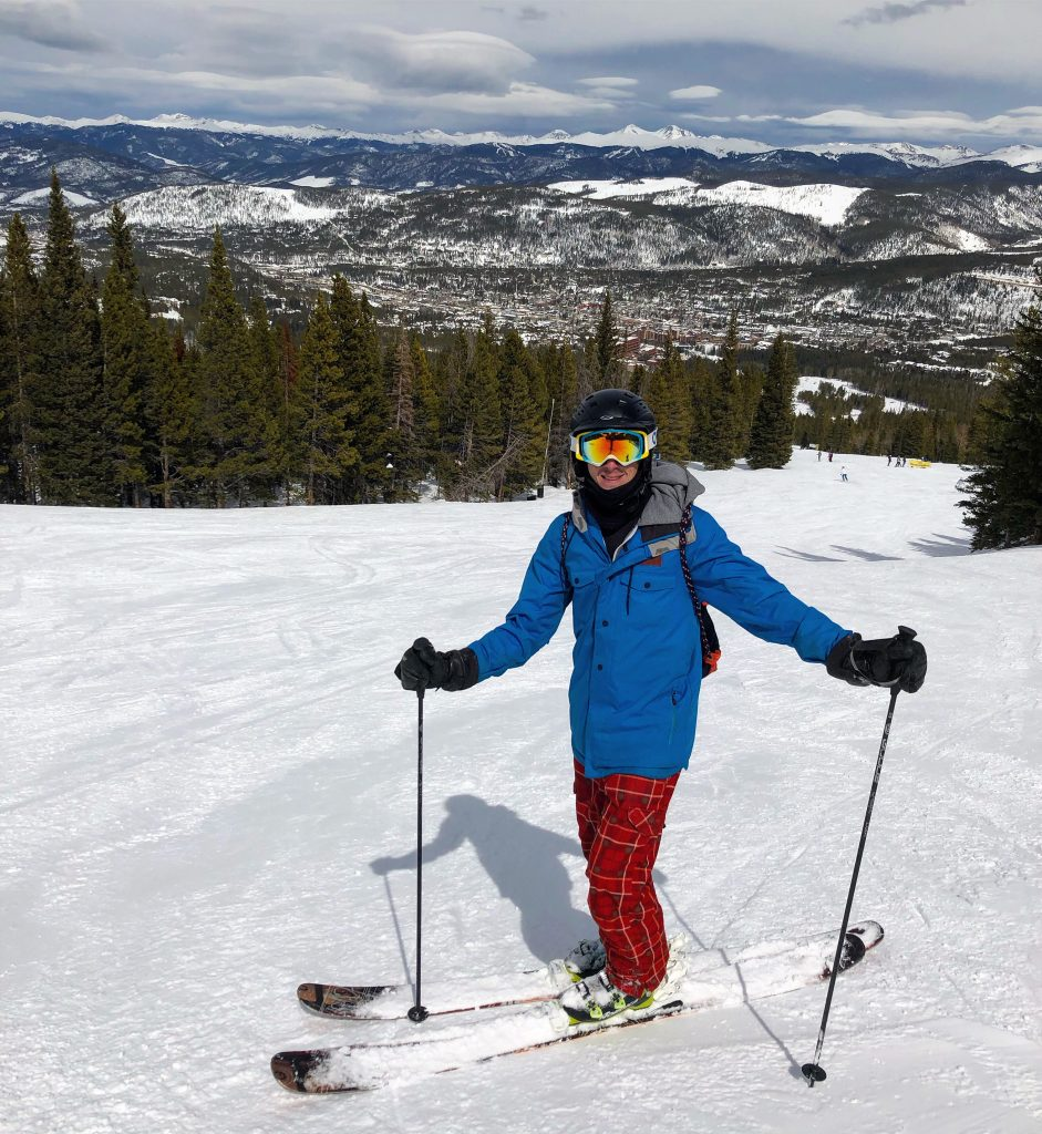 man standing in front of ski slop in Breckenridge for spring skiing
