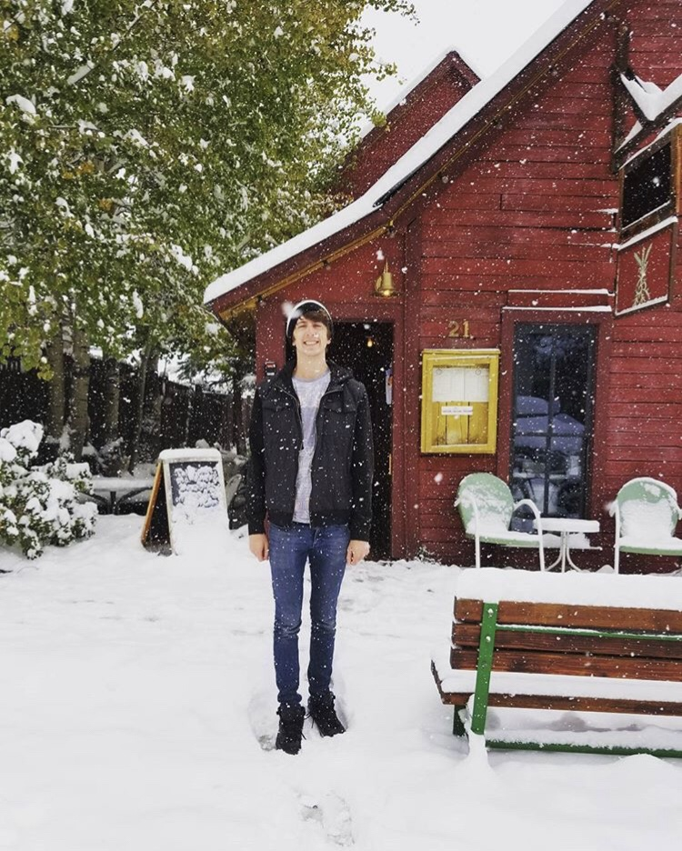 Man standing in front of coffee shop in Crested Butte