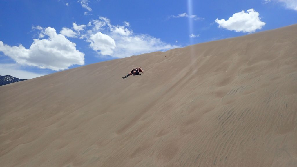 Image: woman laying down trying to slide on dunes at Great Sand Dunes National Park