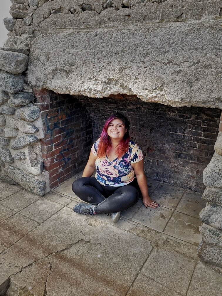 Woman save money by opting outside sitting in outdoor fireplace