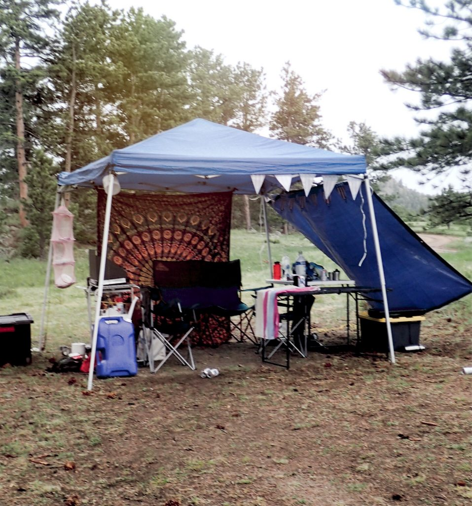 Tent, tarps, and shade set up for camping in the rain